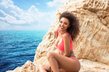 Attractive smiling girl posing on the rocky beach.