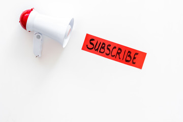 Subscribe template or mockup. Hand lettering subcribe near megaphone on white background top view space for text
