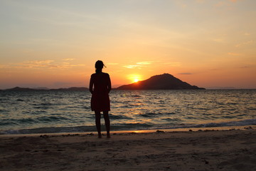 Woman silhouetted in front of sunset at the beach