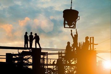 Silhouette of engineer and construction team working at site over blurred background sunset pastel for industry background with Light fair.Create from multiple reference images together. Wall mural