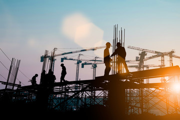 Silhouette of engineer and construction team working at site over blurred background sunset pastel for industry background with Light fair.Create from multiple reference images together.