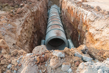 Row of concrete drainage pipe under earth near the construction site.