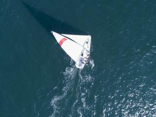 海を渡るヨットの後ろには白い波が立っている。