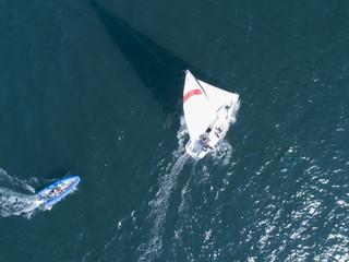海を渡るヨットに近づく小型のボート