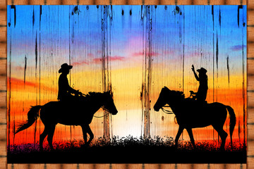 Silhouette of a cowboy riding a wild horse at sunset on a wooden sign