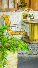 Relaxing area in cozy home garden on summer./ Relaxing area with table set and flower pot decoration near window in cozy home garden on summer.