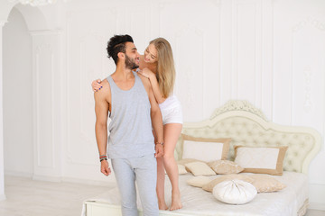 Blonde nice girl kissing hispanic man in badroom in morning. Concept of happy couple and resting on weekends.