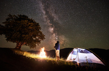 Active female hiker enjoying view of amazing night sky full of stars and Milky way at night camping in the mountains. Back view of woman standing beside campfire and illuminated tent near big tree