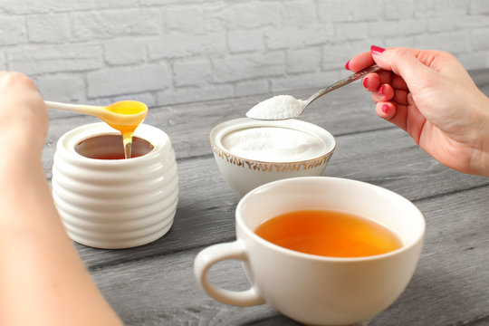 Young woman hands, holding spoon of sugar and honey in other hand deciding what to put in her tea. Artificial vs natural sweetening concept.