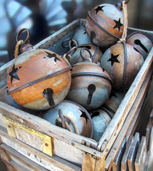 Vintage Christmas Bells at a Texas Flea Market. Large rustic metal ball in retro style lying in a wooden box.