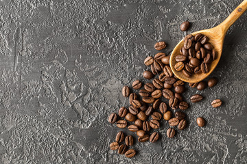 coffee beans in a wooden spoon on stone background
