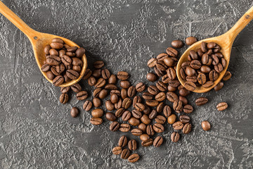 coffee beans in a wooden spoon on stone background.