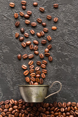 coffee beans and mug on gray concrete background.