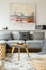 Painting above grey couch in boho living room interior with wooden table and pouf. Real photo