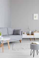 Simple, white and gray living room interior with a book on a stool, wooden table, cozy couch and cupboards. Real photo