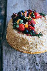 Сake Napoleon decorated with berries of strawberries, grapes, blueberries and physalis on a wooden background
