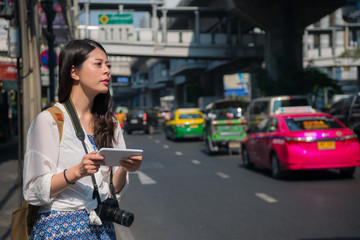 female backpacker waiting for a cab aside the road