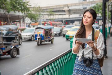 traveller using her touchpad beside the road