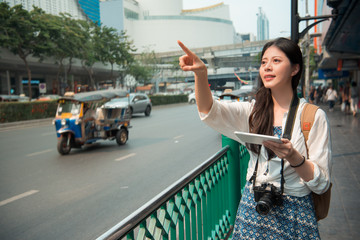 woman stands beside the road and pointing