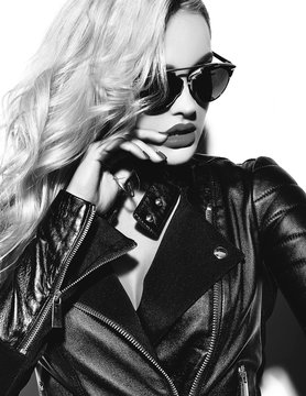 portrait of beautiful happy cute smiling blonde woman bad girl in casual black hipster clothes with red lips in sunglasses