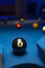 Black billiard ball close to hole over blue felt