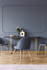 Grey chair at wooden table in minimal dining room interior with wall with molding. Real photo