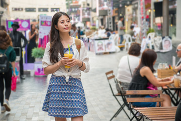 woman holding a cup of mango juice and shopping