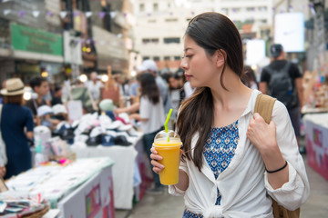 woman holding a cup of mango juice and walking