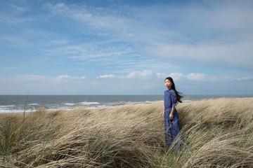 Teen girl standing in tall grass on sea coast
