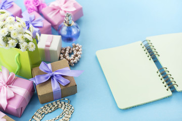 Decorative composition boxes with gifts flowers women's jewelry shopping holiday blue background.