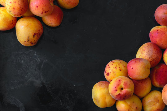 Apricots top view flatlay on dark rustic background; summer