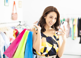woman shopping in clothes store and watching the smartphone