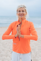 Older fit blond woman doing yoga on a beach