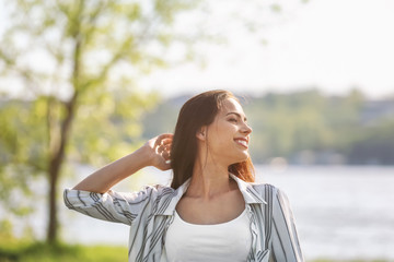 Beautiful young woman near river on spring day