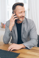 Mature man talking on phone while sitting at table