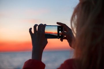 Woman traveler using smartphone and taking photo of colorful sea sunset