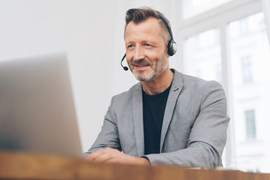 Mature man working with headset in call center