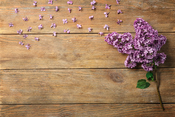 Composition with blossoming lilac on wooden background
