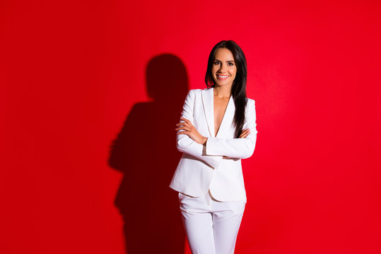 Portrait of cheerful positive woman in white suit holding arms crossed having beaming smile long hair looking at camera isolated on bright red background