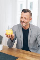 Mature man holding yellow piggy bank at table