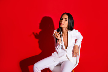 Portrait of pleased delightful woman enjoying smoking cigarette wearing white suit with tempting decolette isolated on bright red background