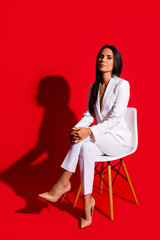 Photoshooting studio concept. Vertical portrait of proud arrogant woman sitting on chair leg by foot looking at camera isolated on vivid red background
