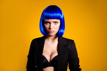 Portrait of stressed depressed woman in vivid blue wig black jacket having big tits looking at camera isolated on yellow background. Relationship life problems troubles concept