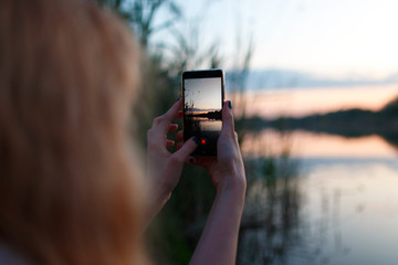 Woman using smartphone and taking photo of colorful sunset above lake
