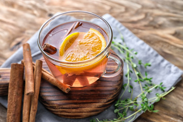 Cup of hot aromatic beverage with cinnamon and orange on wooden board