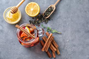 Mason jar of hot aromatic beverage with cinnamon and lemon on table