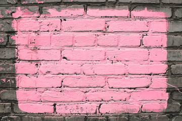 Old realistic dirty brick wall made of pink brick. Uneven brickwork. Center of wall is painted...