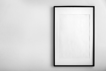 Blank photo frame hanging on white wall