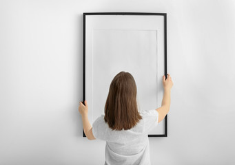 Woman hanging blank photo frame on white wall