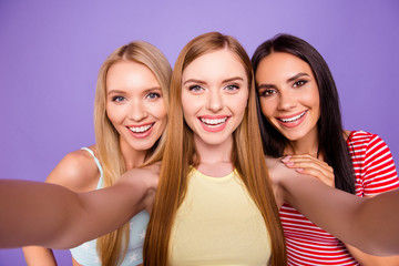 Self portrait of cheerful pretty girls shooting selfie on front camera having leisure isolated on vivid violet background. Vacation weekend rest relax holiday concept